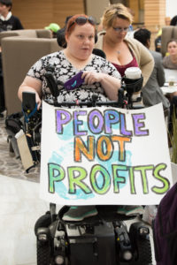 "A NCIL Member carries a sign that reads ""People Not Profits"""