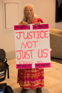 "A NCIL Member carries a sign that reads ""Justice Not Just Us"""