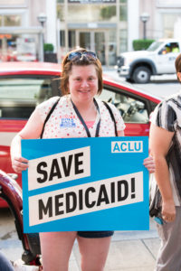 "A NCIL Member holds a sign that reads ""Save Medicaid"""