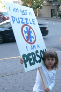 "A young girl holds a protest sign that says ""I am not a puzzle - I am a person"""