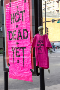 Not Dead Yet Banner Hanging Next to A Skeleton Wearing a NDY T-Shirt