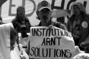 """A black and white photo of a person carrying a sign that reads """"Institutions Aren't Solutions"""""""