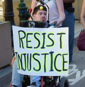 "A NCIL Member holds a sign that says ""Resist Injustice"""