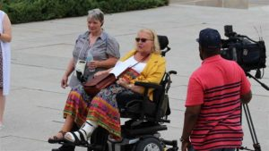 Kathy Hoell sits in her wheelchair in front of a cameraman. A woman walks to her right.